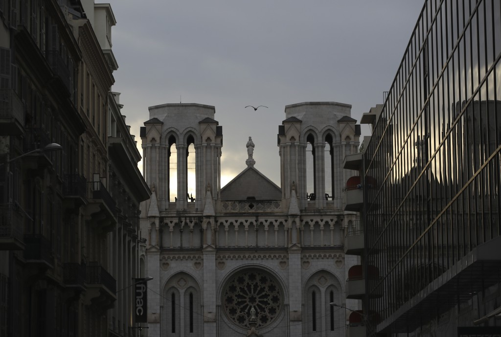 The sun reflects off of an adjacent building as the daylight begins to fade on a street outside the Notre Dame church in Nice, southern France, after ...