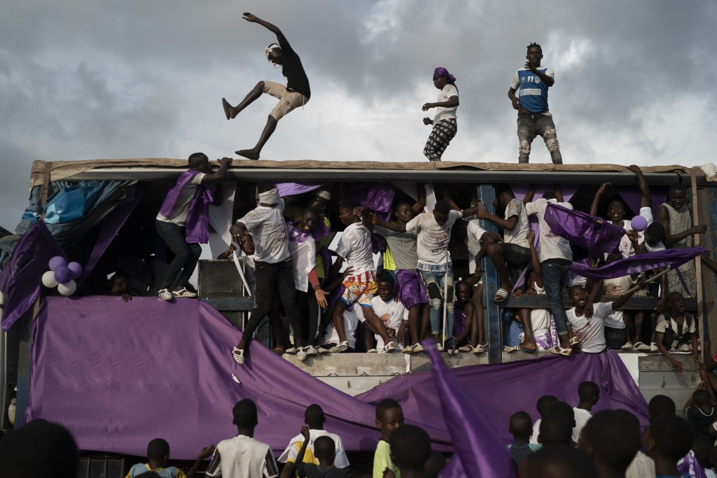 Supporters of the presidential candidate Kouadio Konan Bertin, dance over a sound truck during the final campaign rally in Abidjan, Ivory Coast, Thurs...