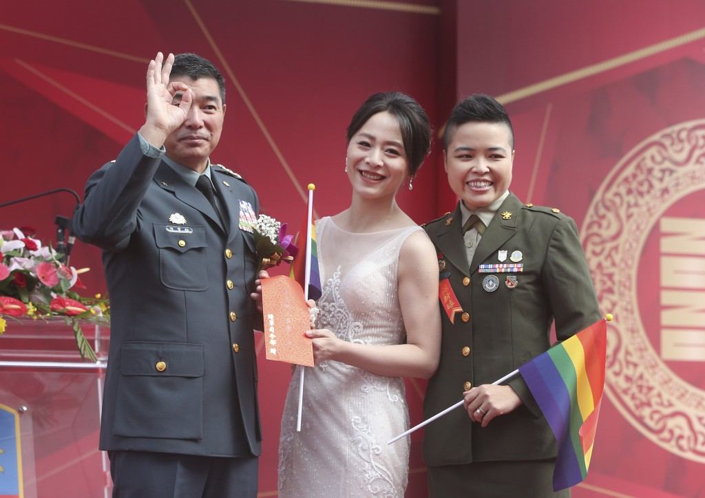 Lesbian couple Yi Wang, right, Yumi Meng and General Chen Pao-Yu pose for a photo during a military mass weddings ceremony in Taoyuan city, northern T...