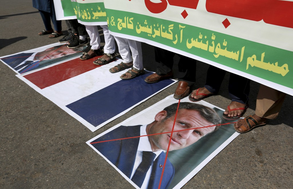 Supporters of the Muslims Students Organization stand on a representation of a French national flag and defaced images of French President Emmanuel Ma...