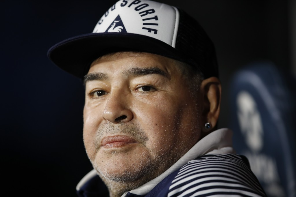 FILE - In this March 7, 2020 file photo, Diego Maradona, coach of Gimnasia y Esgrima, sits on the bench prior to Argentina's soccer league match again...
