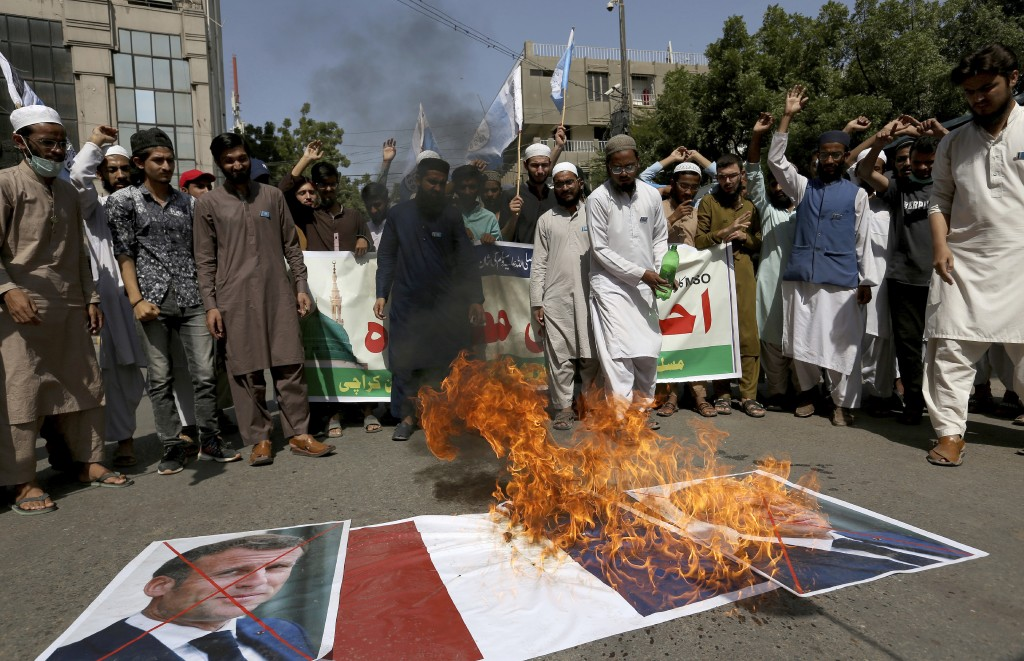 Supporters of the Muslims Students Organization burn a representation of a French national flag and defaced images of French President Emmanuel Macron...