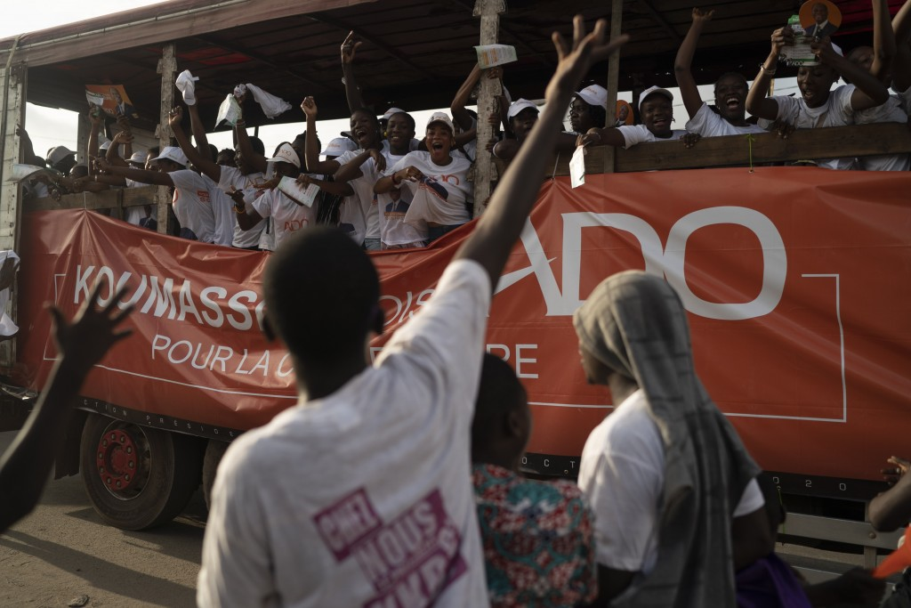 A supporter of the presidential candidate Kouadio Konan Bertin reacts as supporters of the Ivory Coast President Alassane Ouattara, ride a truck, duri...