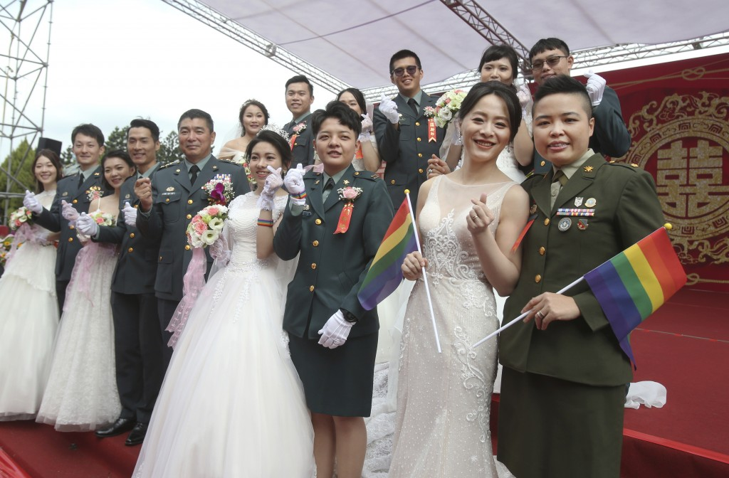 Two lesbian couples, from right to left, Yi Wang and Yumi Meng, Chen Ying-hsuan and Li Li-chen pose for a photo during a military mass weddings ceremo...