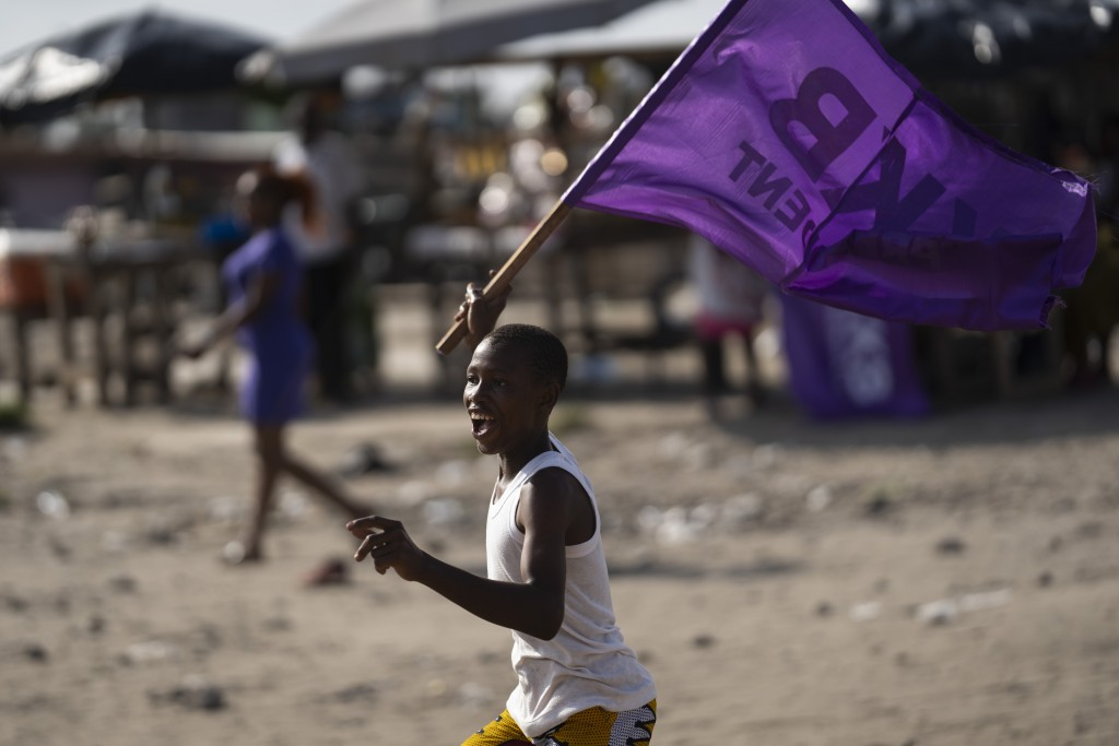 A boy runs as he waves a flag in support of the presidential candidate Kouadio Konan Bertin, during the final campaign rally in Abidjan, Ivory Coast, ...
