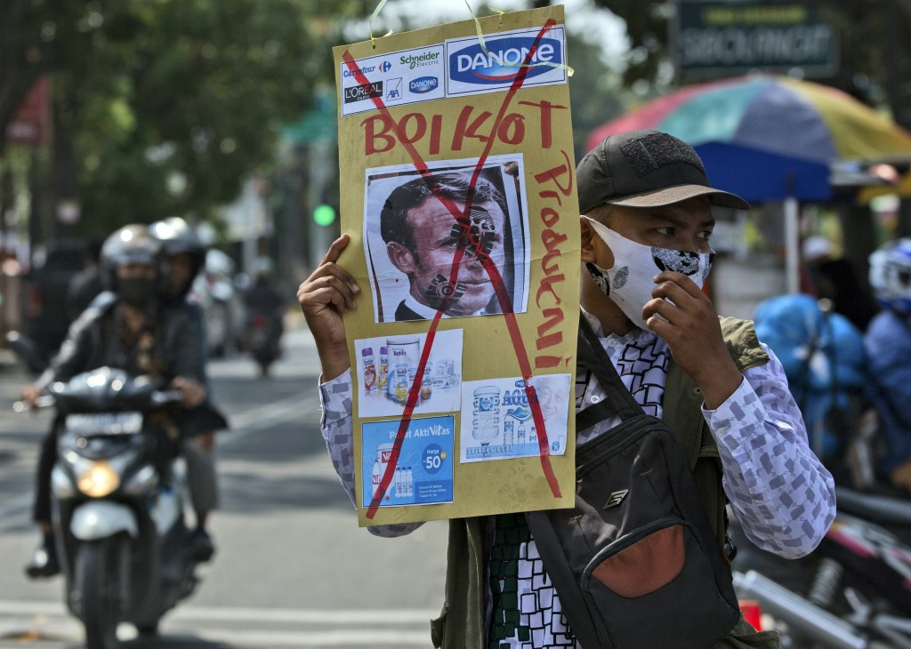 A Muslim man holds a defaced poster of French President Emmanuel Macron during a protest at Al Jihad mosque in Medan, North Sumatra, Indonesia, Friday...