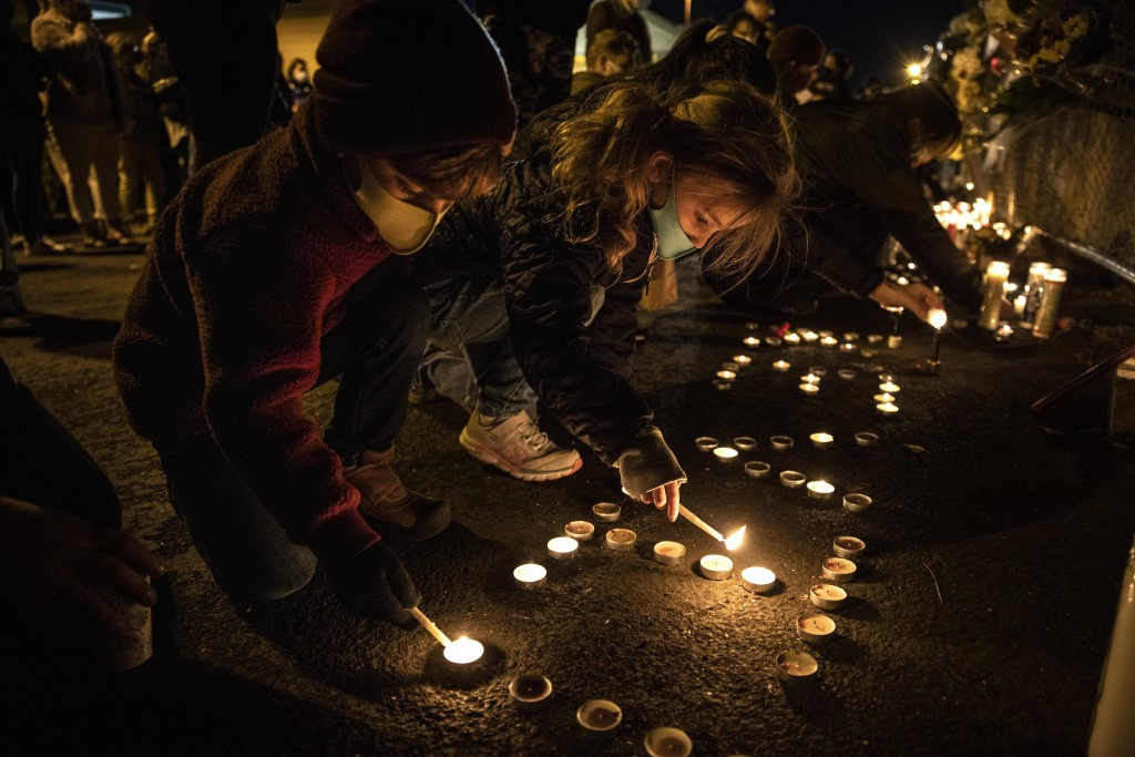 Children light candles as people gather for Kevin Peterson Jr., who was killed in Thursday's shooting with police involved, at a candlelight vigil in ...