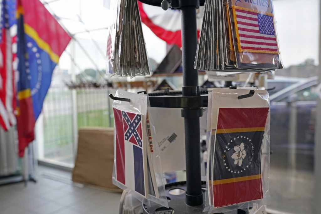 A display stand has both the recently retired Mississippi state flag, left, and the magnolia centered banner that was chosen by the Mississippi State ...