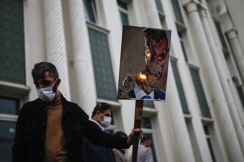 A man holds a poster with a caricature of France's President Emmanuel Macron, depicting him as a devil, which was set on fire, during a protest agains...