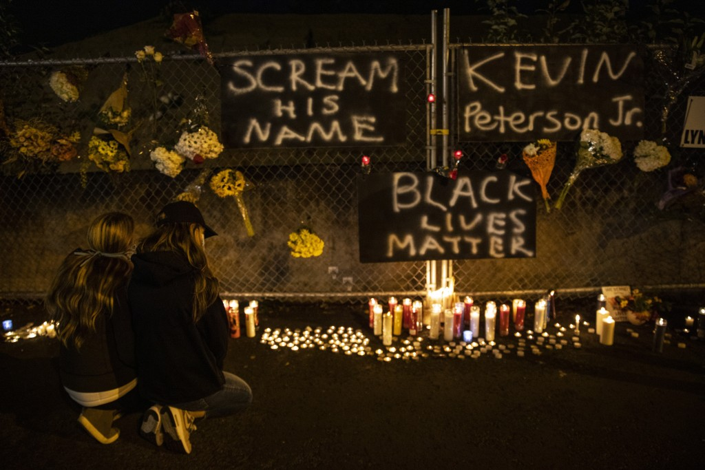 People gather for Kevin Peterson Jr., who was killed in Thursday's shooting with police involved, at a candlelight vigil in Vancouver, Wash.,  Friday,...