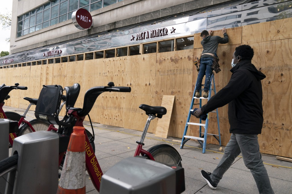 A pedestrian passes work being done to board up a Pret A Manger restaurant along K Street, Friday, Oct. 30, 2020, ahead of the presidential election, ...