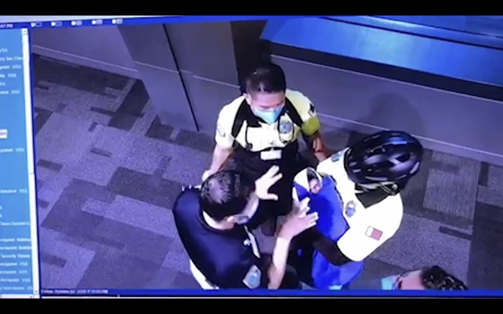 This image made from the Oct. 2, 2020, surveillance camera footage obtained by the website Doha News shows officials care for an abandoned baby at Ham...