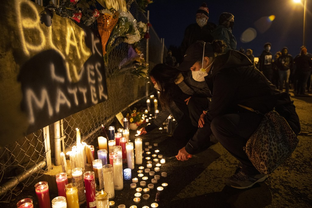 A woman lights a candle as people gather for Kevin Peterson Jr., who was killed in Thursday's shooting with police involved, at a candlelight vigil in...