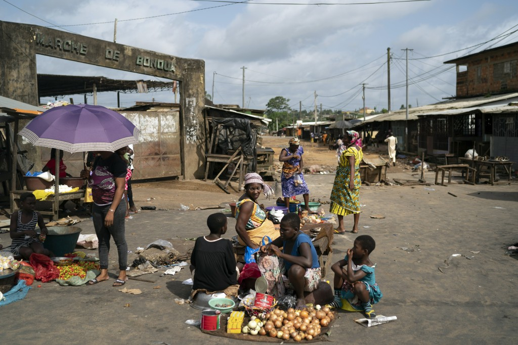 A woman sits next her goods to sale on a street market in Bonoua, in the outskirts of Abidjan, Ivory Coast, Friday, Oct. 30, 2020. Opposition activist...