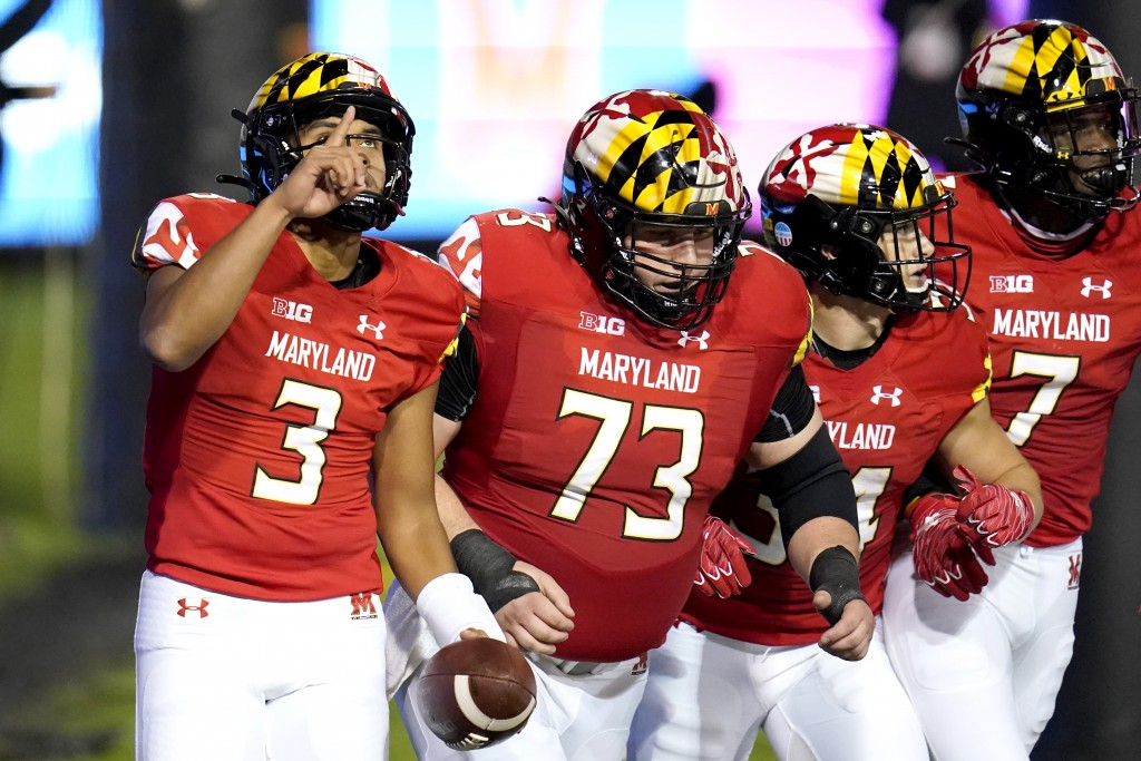 Maryland quarterback Taulia Tagovailoa, far left, reacts after scoring a touchdown on a run against Minnesota during the first half of an NCAA college...