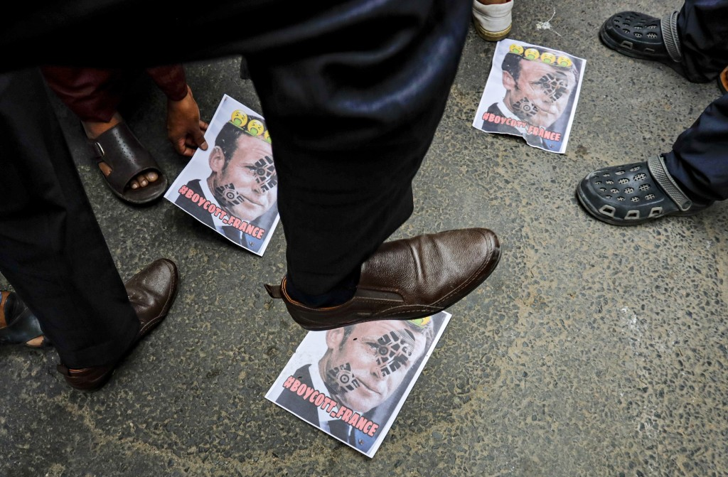 A Muslim activist stamps on posters bearing defaced images of French President Emmanuel Macron during a protest near the French Consulate, in Kolkata,...
