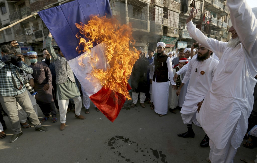 Supporters of religious group burn a representation of a French flag during a rally against French President Emmanuel Macron and republishing of caric...