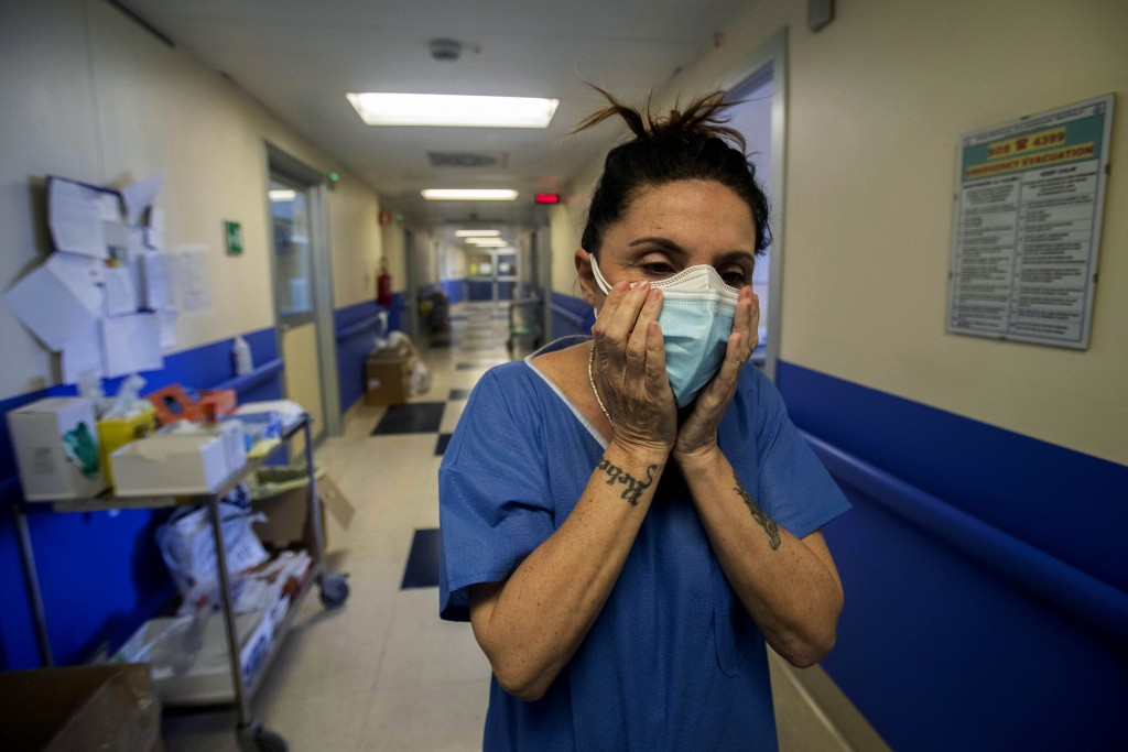Nurse Cristina Settembrese fixes two masks to her face at the San Paolo hospital in Milan, Italy on April 10, 2020.