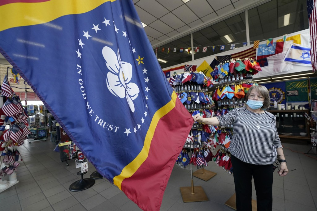 Brenda McIntyre, a co-owner of A Complete Flag Source store in Jackson, Miss., shows off, Tuesday, Oct. 27, 2020, the magnolia centered banner chosen ...