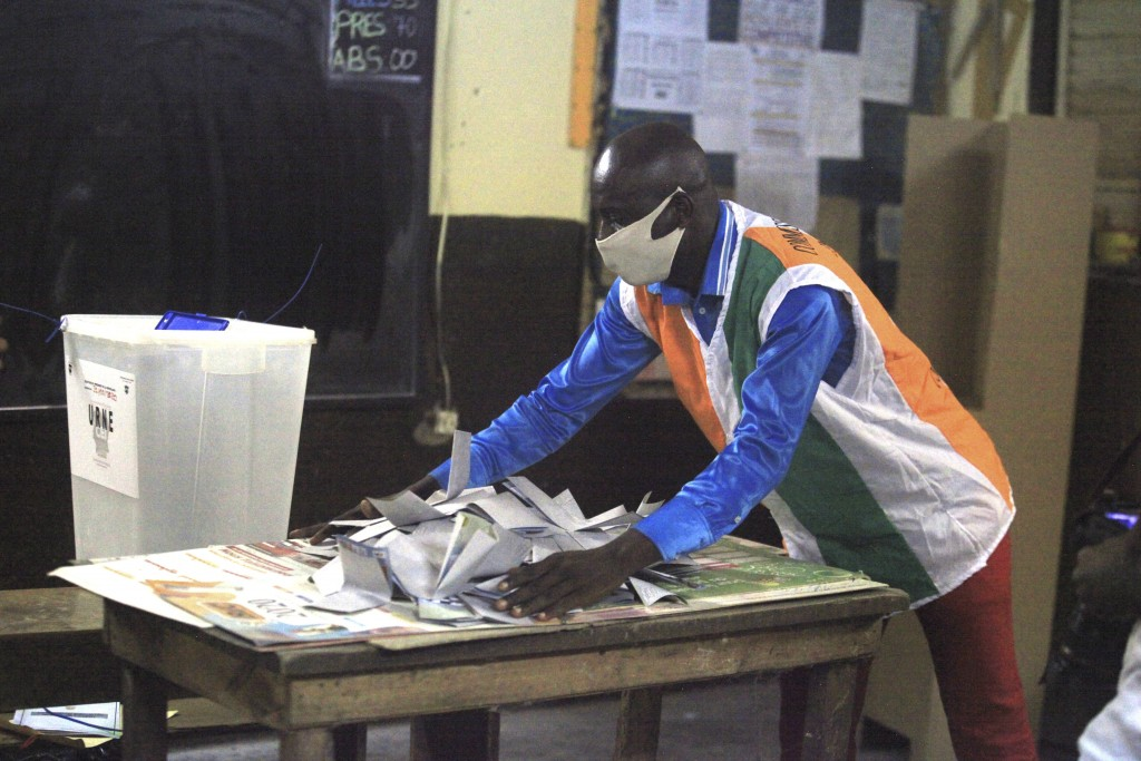 Electoral commission officials count votes for the presidential election in Abidjan, Ivory Coast, Saturday, Oct. 31, 2020. Some tens of thousands of s...