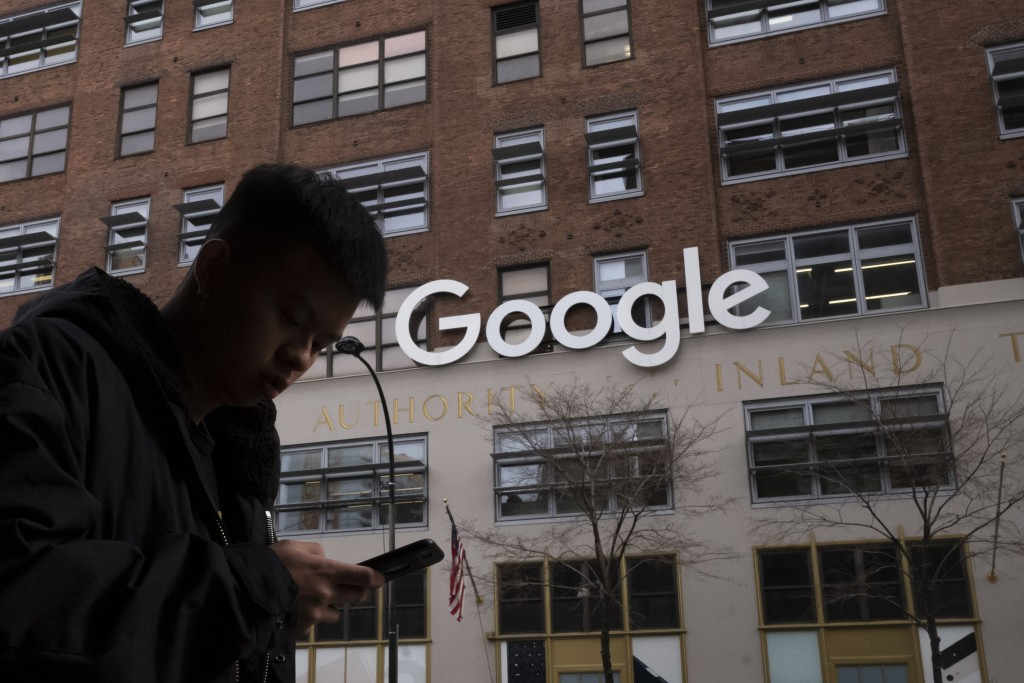 FILE - In this file photo dated Monday, Dec. 17, 2018, a man using a mobile phone walks past Google offices in New York. Monopoly or not, small busine...
