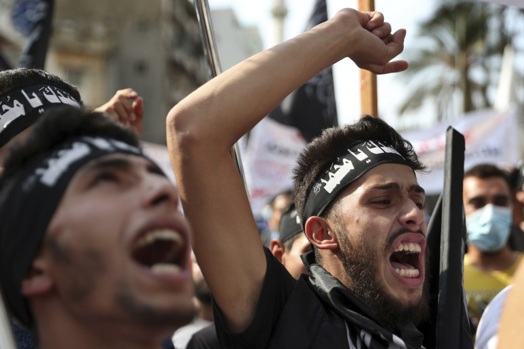 "FILE - In this Oct.30 2020 file photo, protesters chant slogans as they wear headbands with Arabic that read: ""We are your soldiers, Oh Muhammad,"" dur..."