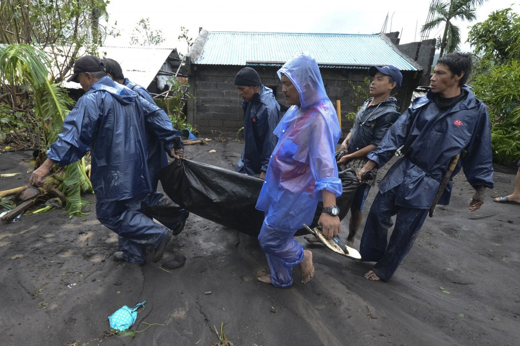 Rescuers carry the body of a man that drowned in floods as Typhoon Goni hit Guinobatan, Albay province, central Philippines, Sunday, Nov. 1, 2020. The...