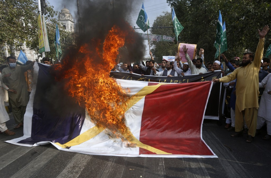 FILE - In this Oct.30, 2020 file photo, supporters of religious group burn a representation of a French flag during a rally against French President E...