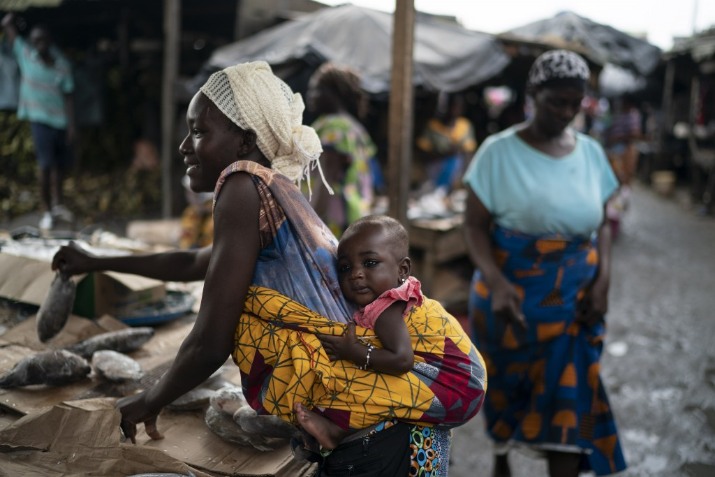 A woman carries her baby as she places fishes for sale at a market in Abobo neighborhood, in the suburbs of Abidjan, Ivory Coast, Sunday, Nov. 1, 2020...