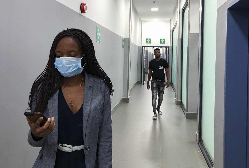 FILE — In this Feb. 6, 2020, file photo, a masked woman walks in a corridor of a shopping mall in Kitwe, Zambia.  Facing financial difficulties aggrav...