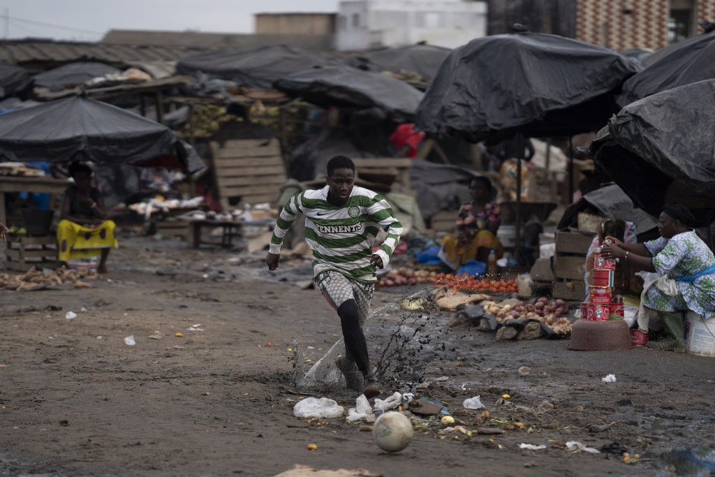 A youth runs after the ball as he plays soccer at a local market in Abobo neighborhood, in the suburbs of Abidjan, Ivory Coast, Sunday, Nov. 1, 2020. ...