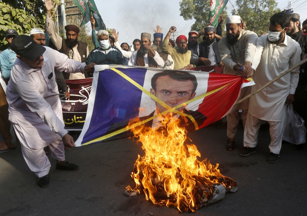 Supporters of Sunni Tehreek, a religious group, burn a representation of a French flag with a defaced image of French President Emmanuel Macron during...