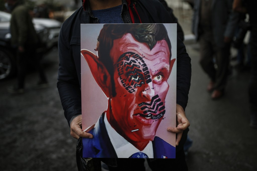 FILE - In this Oct.30, 2020 file photo, a man holds a poster with a caricature of France's President Emmanuel Macron, depicting him as devil during a ...