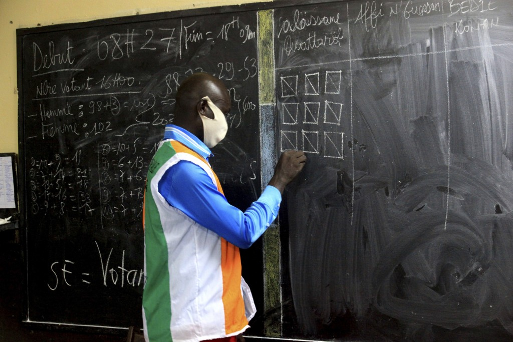Electoral commission officials count the votes for the presidential election in Abidjan, Ivory Coast, Saturday, Oct. 31, 2020. Some tens of thousands ...