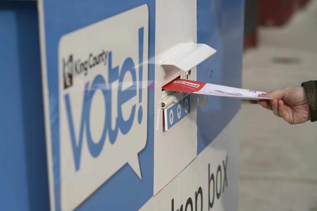 圖為美國西雅圖一民眾10月27日提前投票,將票投入票箱場景。(美聯社圖片)