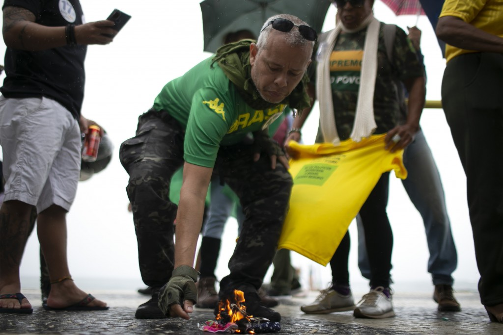 Supporters of Brazilian President Bolsonaro burn protective masks while rallying in favor of Bolsonaro's position that no one will be forced to use th...