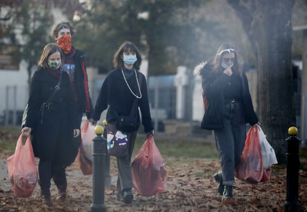 People walk with flowers they have bought, after Poland's government closed all cemeteries in an attempt to curb the spread of COVID-19, in Warsaw, Po...
