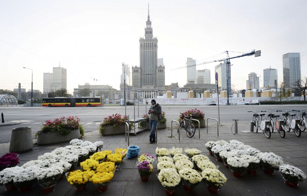 A man stands by bouquets of flowers, after Poland's government closed all cemeteries in an attempt to curb the spread of COVID-19, in Warsaw, Poland, ...