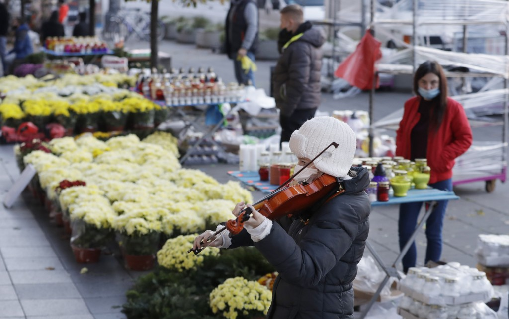 A woman plays the violin near to people buying flowers, after Poland's government closed all cemeteries in an attempt to curb the spread of COVID-19, ...