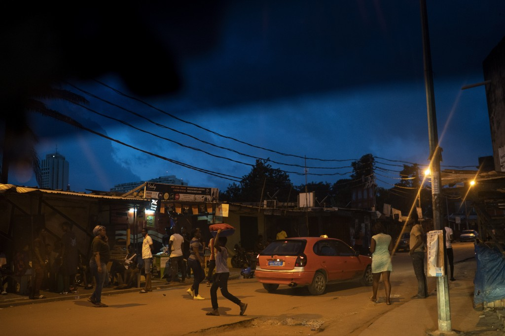 People cross a street at Blockhaus neighborhood during the dusk in Abidjan, Ivory Coast, Sunday, Nov. 1, 2020. Ivory Coast residents braced for more u...