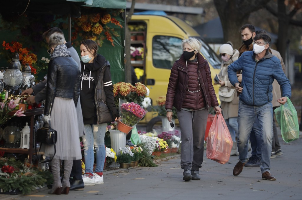 People buy flowers, after Poland's government closed all cemeteries in an attempt to curb the spread of COVID-19, in Warsaw, Poland, Sunday, Nov. 1, 2...