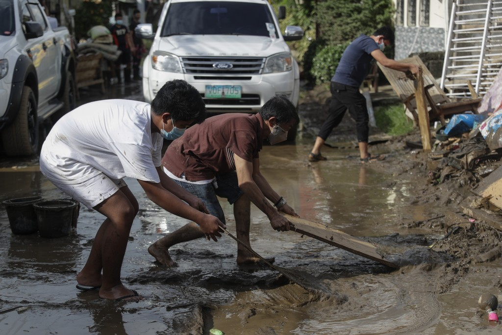 Residents use wood to clear out a mud-covered road after floodwaters caused by Typhoon Goni rose inside their village in Batangas city, Batangas provi...