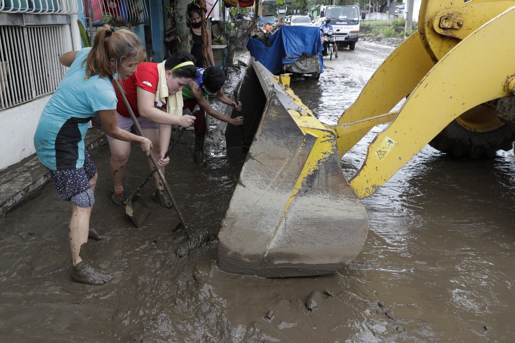 Residents use shovels to push mud inside a bulldozer as they try to clear out their area after floodwaters caused by Typhoon Goni rose inside their vi...