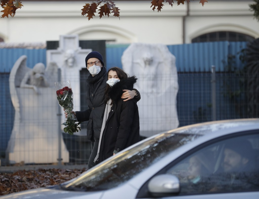 A couple walk by a cemetry holding flowers, after Poland's government closed all cemeteries in an attempt to curb the spread of COVID-19, in Warsaw, P...