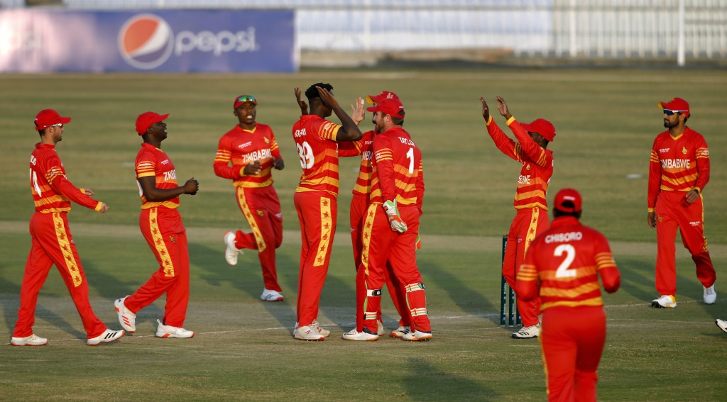 Zimbabwe's pacer Richard Ngarava, center without cap, celebrates with teammates after taking wicket of Pakistani batsman Haider Ali during their 3rd o...