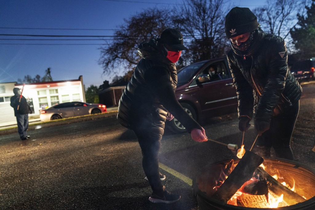 Volunteers Latrina Lawrence, left, and Breya Smith, roast marshmallows for motorists pulling through a drive-thru socially distanced Halloween celebra...