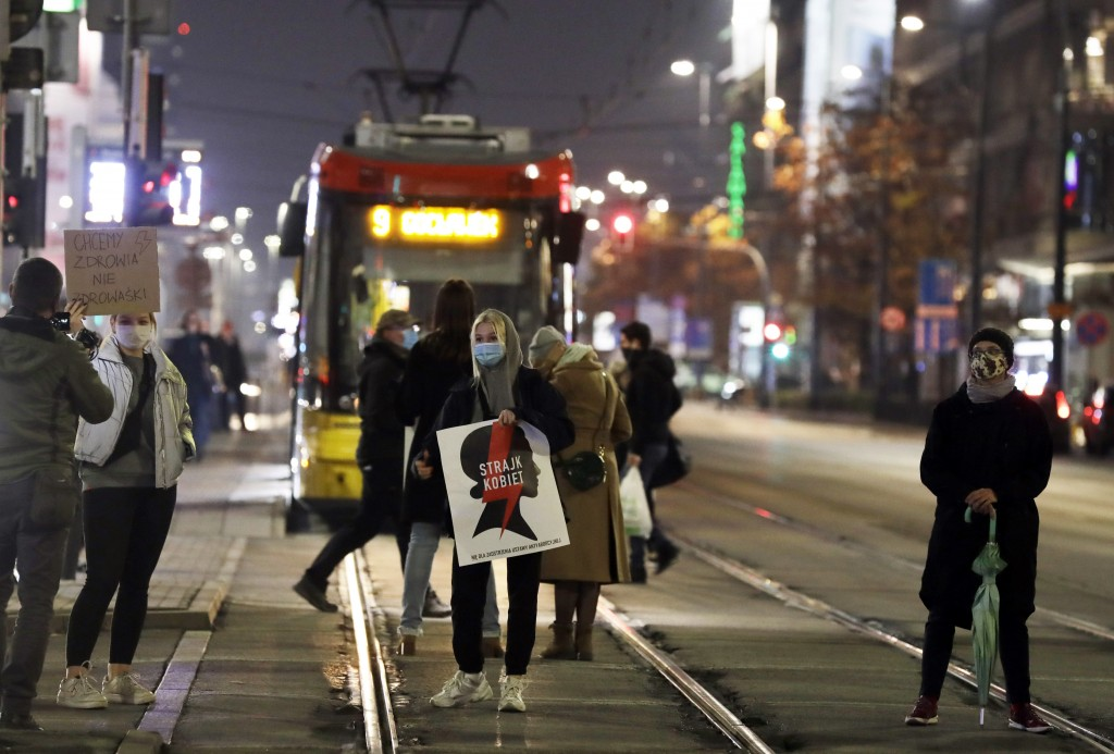 """Protesters hold signs reading in Polish """"women's strike"""" as they block a crossing in downtown Warsaw, Monday, Nov. 9, 2020, on the 12th straight day o..."""