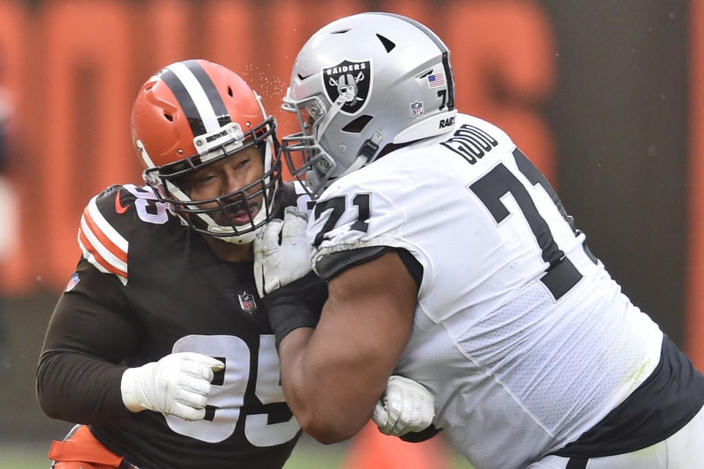 Cleveland Browns defensive end Myles Garrett, left, and Las Vegas Raiders offensive tackle Denzelle Good collide during the first half of an NFL footb...