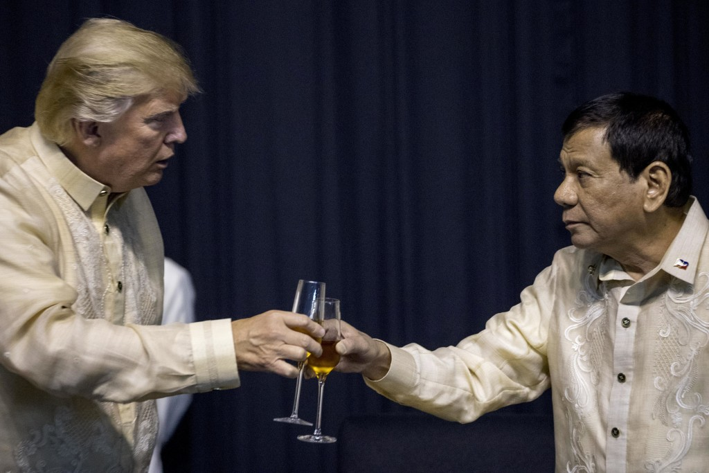 FILE - In this Nov. 12, 2017 photo, President Donald Trump toasts with Philippines President Rodrigo Duterte, right, as they wear the Philippine tradi...