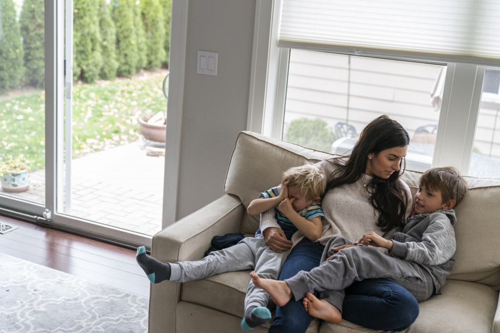 Meghan Iliesiu sits with her sons, Gabriel, 6, right, and Alexander, 4, at their home in Huntington Woods, Mich., Friday, Oct. 30, 2020. Iliesiu, a 32...